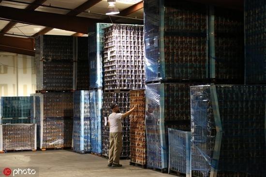 资料图:美国佛罗里达州某啤酒厂,工作人员正在检查装有空铝罐的架子 图自IC photo