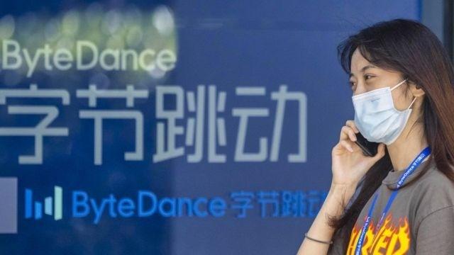 上海字节跳动办公楼外一名女士在用手机通电话(3/8/2020)